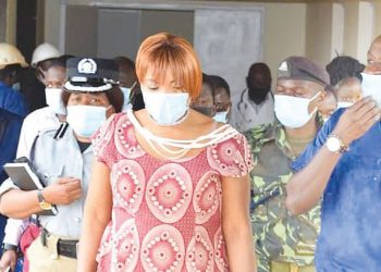 Kanyasho (C) and other officials are briefed by a healthcare worker during the tour