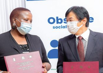 Chiponda and Satoshi pose with copies of signed commitments on the project