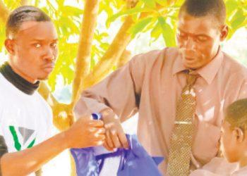 Hara (L) hands over a uniform to Ng'oma