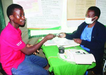Rosario (L) receives male condoms from a health service provider