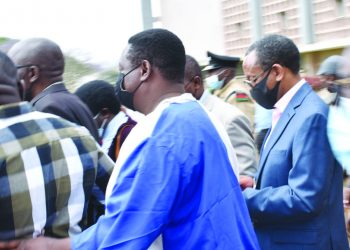 Mpinganjira (R) being escorted to the police van by sympathisers