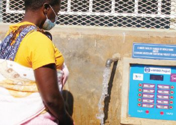 A woman draws water from one of the kiosks
